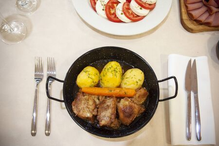 cooked beef with boiled potatoes and carrots served in a metal container, top view