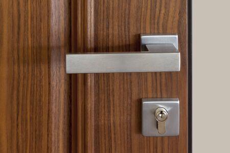 metal door handle and lock on wooden door, close up Stockfoto
