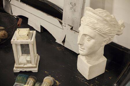 white antique plaster female head on black desk