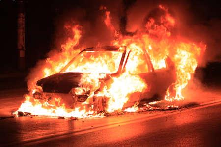 Burning car on the road photo