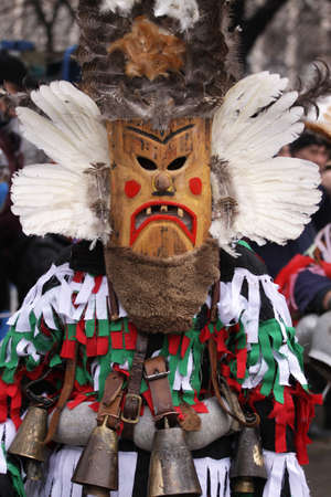 Pernik, Bulgaria - January 25, 2014: Unidentified boy with traditional Kukeri costume are seen at the the International Festival of the Masquerade Games Surva in Pernik, Bulgaria. Surva takes place the last weekend of January and its the biggest event of