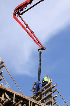 concrete pump: Builder worker with tube from truck mounted concrete pump pouring cement into formwork reinforcement