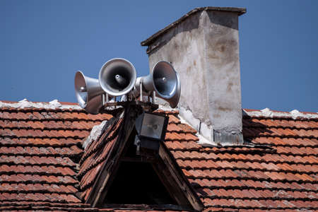 Six megaphones in blue sky on the roof background