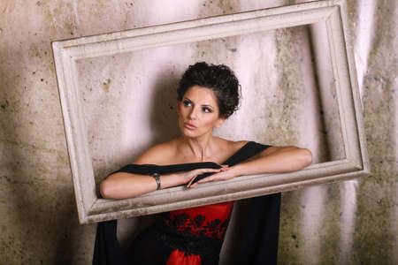 lampara magica: Beautiful woman in a red and black dress posing in a picture frame