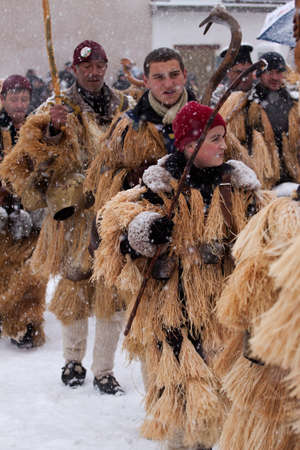 ethnic customs: Breznik, Bulgaria - January 16, 2016: Unidentified boy with traditional Kukeri costume are seen at the Festival of the Masquerade Games Surova in Breznik, Bulgaria. Surova takes place the third weekend of January and its the biggest event of this type in