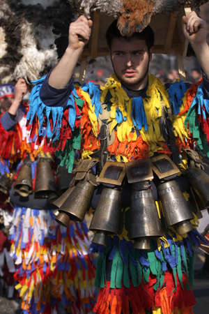 ethnic customs: Pernik, Bulgaria - January 30, 2016: Unidentified boy with traditional Kukeri costume are seen at the Festival of the Masquerade Games Surova in Pernik, Bulgaria. Surva takes place the third weekend of January and its the biggest event of this type in Bu