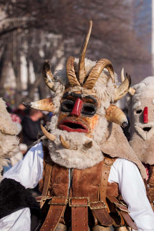customs and celebrations: Pernik, Bulgaria - January 30, 2016: Unidentified boy with traditional Kukeri costume are seen at the Festival of the Masquerade Games Surova in Pernik, Bulgaria. Surva takes place the third weekend of January and its the biggest event of this type in Bu