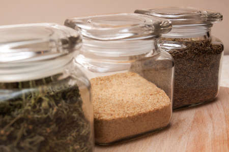 a jar stand: Glass jars with some spices on a wooden stand.