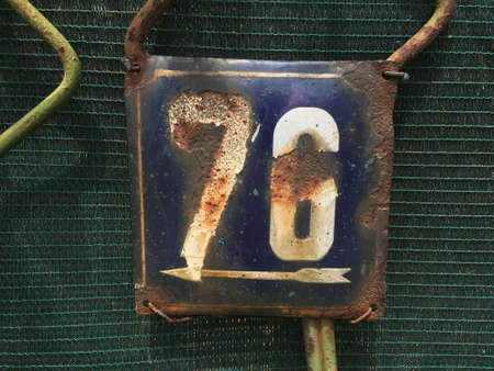 Vintage grunge square metal rusty plate of number of street address with number closeup