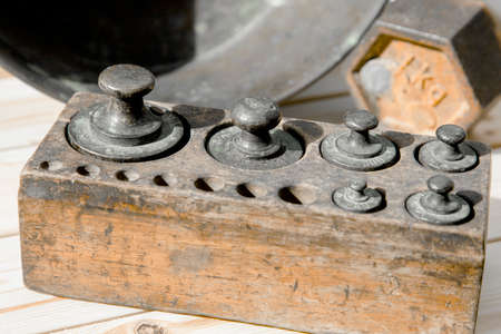 Old rusty scale weight on wooden table, Old rusty iron scale weight