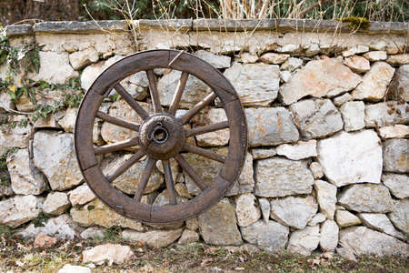 Old wooden wagon wheel hanging against a stone wall