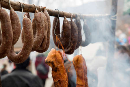 Bulgarian,home made sausages and fillet hanging on wooden sticks, Home sausage over steaming grill Stock Photo