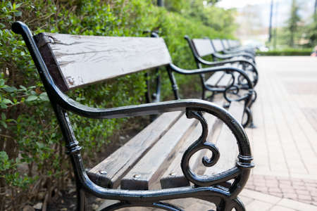 A row of wood and metal benches along a walkway in a park.