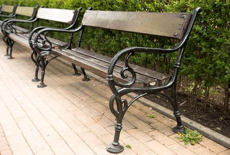 Une rangée de bancs en bois et en métal le long d'une allée dans un parc. Banque d'images