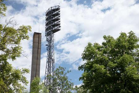 Tall lights standing to illuminate a football field. Shot against blue sky. Lights at a sports stadium.