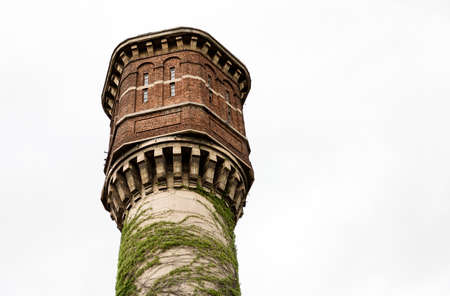 A close look at an old abandoned brick and concrete water tower overgrown with ivy. Sofia, Bulgaria.
