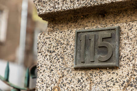 A stone wall with the street number one hundred and fifteen on it.