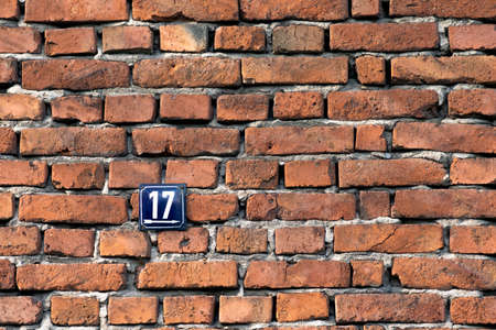Number seventeen, a metal sign on a red brick wall of a house.
