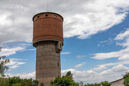 A close look at an old abandoned brick and concrete water tower overgrown with ivy. Sofia, Bulgaria