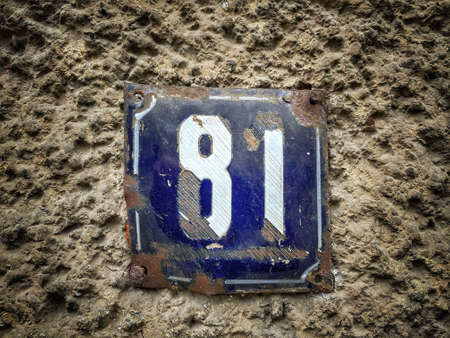 Number 81, the number of houses, apartments, streets. The white number on a blue metal plate, house number eighty-one (81) on a rough wall.