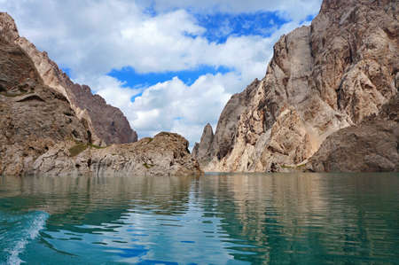 grandiose: Fine Kelsu mountain lake with grandiose rocks and the dark blue sky with clouds    Kelsu, Kyrgyzstan