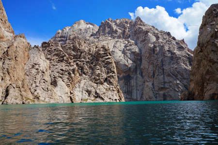 grandiose: wonderful high rocks both grandiose high-mountainous lake and blue sky with clouds - Kelsu, Kyrgyzstan