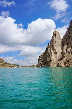 grandiose: Grandiose rocks and Kelsu mountain lake against the background of colourful dark blue sky with clouds... Kelsu, Kyrgyzstan Stock Photo