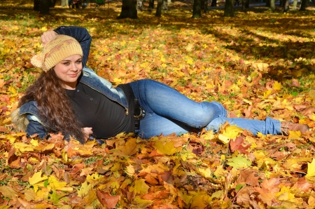 women jeans: Young woman lying in bright autumn leaves and smiling
