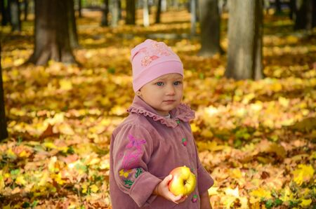 Little lovely girl holding an apple with bright autumn park on a background photo