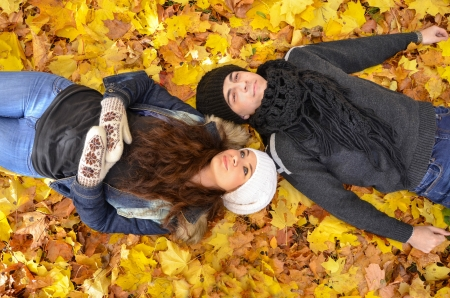 Young couple relaxing on autumn leaves photo