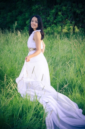 Wedding look of a young woman in the grass photo