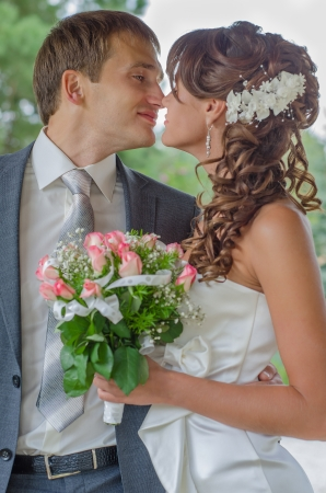 Happy young bride and groom embrace and kiss photo