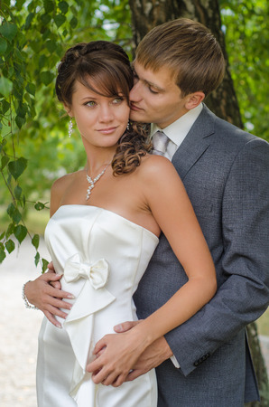 Wedding couple embracing among twisted bush branches photo
