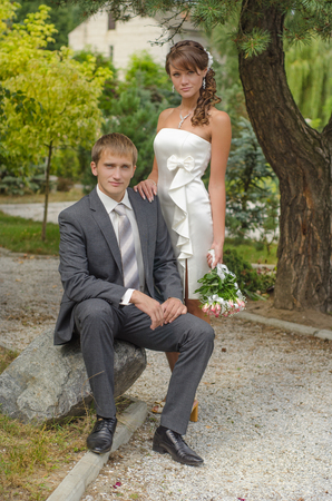 Bride and groom sitting on a stone photo