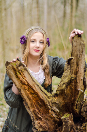 Girl standing in the forest near crashed tree photo