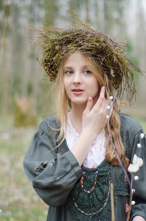 circlet: Ritratto di una ragazza in stile medievale folk con una coroncina di fiori di toccare il viso