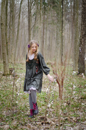 girl in a folk  medieval style walking in the forest photo