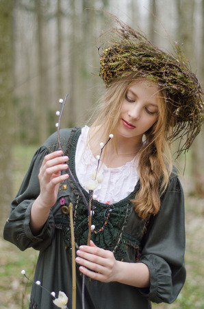 circlet: Portrait of a girl in a folk  medieval style with a circlet of flowers looking at the willow branch Stock Photo