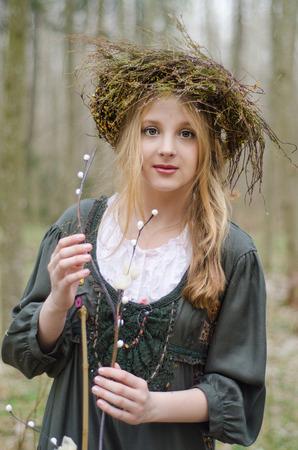 circlet: Ritratto di una ragazza in stile medievale folk con una coroncina di fiori che tocca ramo di salice