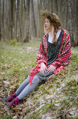 circlet: folk style picture of a girl in a circlet of flowers sitting in the forest covered with colorful cape Stock Photo