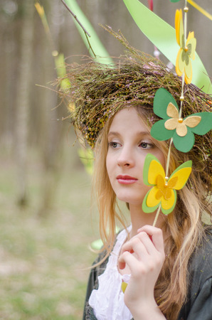 circlet: Close up portrait of a girl in a folk   circlet of flowers holding garland of butterflies