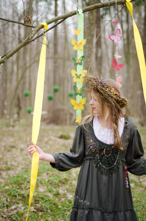 circlet: Picture of a pretty girl in a folk   circlet of flowers holding garland of butterflies in the forest