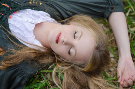Close up portrait of a girl sleeping on the grass photo