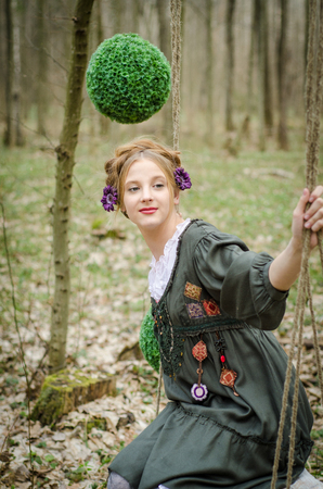 Picture of a young pretty girl on a swing in the forest with decorative green balls on background photo