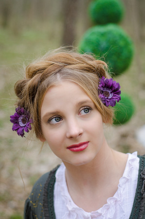 Portrait of a pensive young girl  with decorative flowers in her hair photo