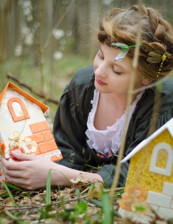 doll house: Girl lying on the grass and looking at vintage doll house Stock Photo