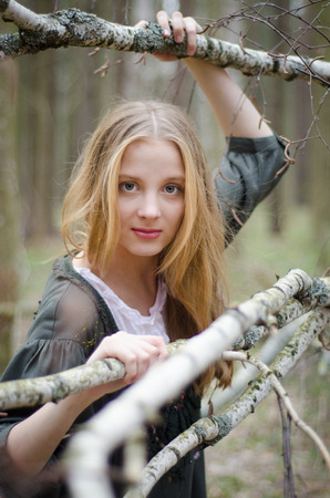 Picture of beautiful blonde girl touching birch branches photo