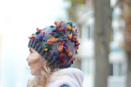 Picture of a blonde toddler girl in the funny knitted hat