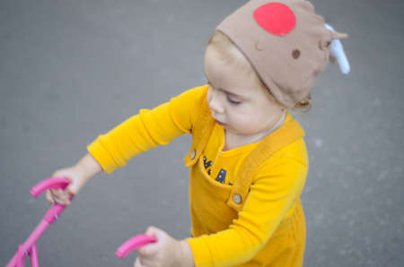 Photo of a toddler girl in the funny hat playing with a toy stroller