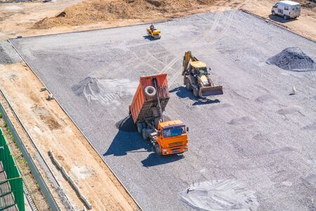 dumptruck: Dump truck unloads asphalt at the construction site of the school stadium Stock Photo